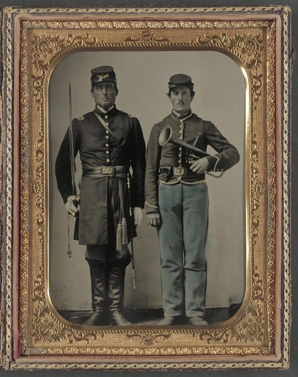 Photographie représentant deux soldats au garde à vous. L'un porte une épée, l'autre un clairon.