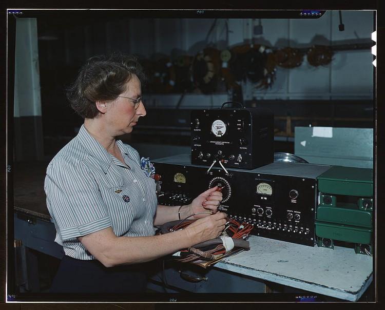 Une opératrice travaille au branchement de fils électriques.