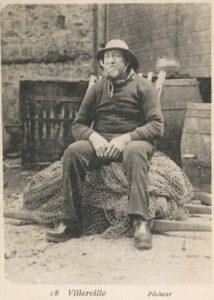 Photographie ancienne montrant un pêcheur assis sur un filet, fumant la pipe.